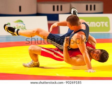 BUCHAREST, ROMANIA - JULY 25: Unidentified wrestlers fight during Junior Wrestling World Championship on July 25, 2011, Bucharest, Romania