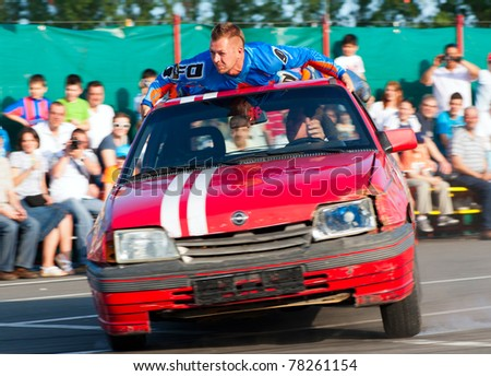BUCHAREST, ROMANIA - MAY 29: Unknown driver  and stuntman entertain the crowds at ''Stunt Cars Show'' on May 29, 2011 in Bucharest, Romania