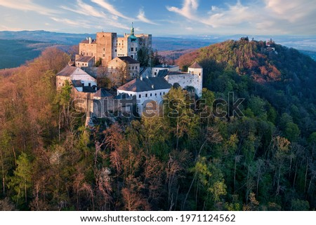 Buchlov Castle. Aerial view on monumental castle in Romanesque Gothic style, standing on a wooded hill against Saint Barbara's Chapel on the hill in background. Spring, tourism hot spot. Czech castles