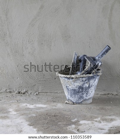 bucket and a trowel on a wall background