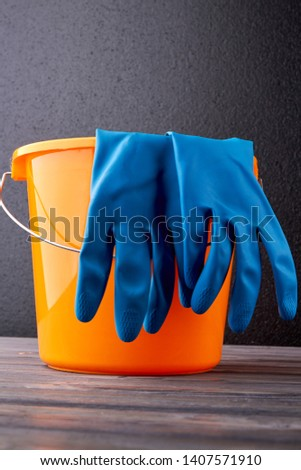 Bucket and gloves for cleaning on dark background. Household chores concept. #1407571910