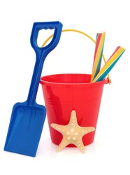 Bucket and spade plastic beach toy in red and blue with stick of rock and starfish over white background.