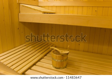 Bucket for water and pillows on benches in Finnish sauna.