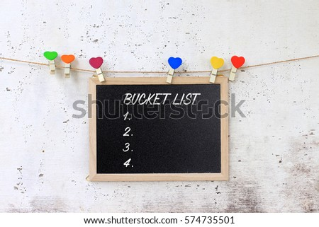Bucket list - words on the blackboard hanging with rope on rustic wooden background