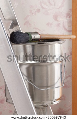 Bucket of paint and brush on stepladder #300697943
