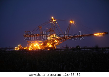 bucket wheel excavator digging for brown coal night view Poland extractive industry