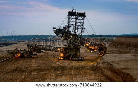 Bucket wheel excavator in the coal mine on the sunset. Huge coal mining drill machine in open pit