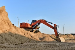 Bucket wheel excavator on earthmoving at construction site. Backhoe digs sand on blue sky background. Construction machinery for excavation, loading, lifting and groundwork on job sites.