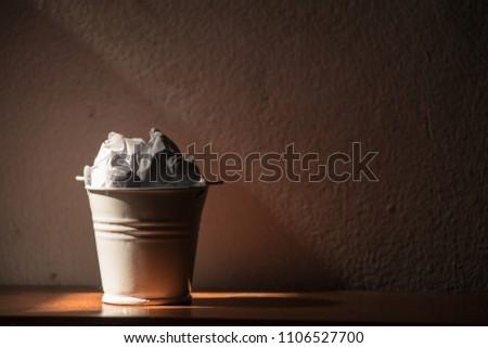 bucket white garbage paper  dark background #1106527700