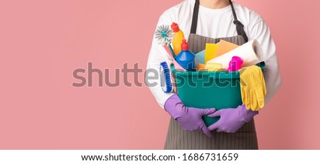 Photo of Bucket with cleaning supplies and tools in hands of unrecognizable man in apron standing on pink background, cropped image, panorana with free space