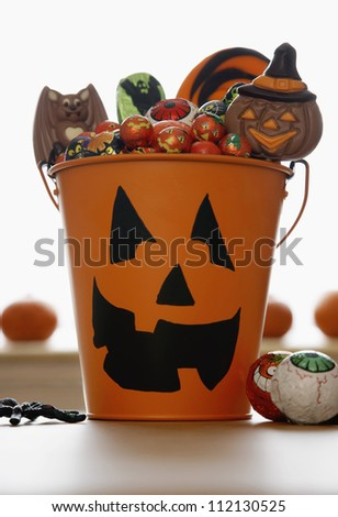 stock photo : Bucket with Jack O'lantern face filled with sweets