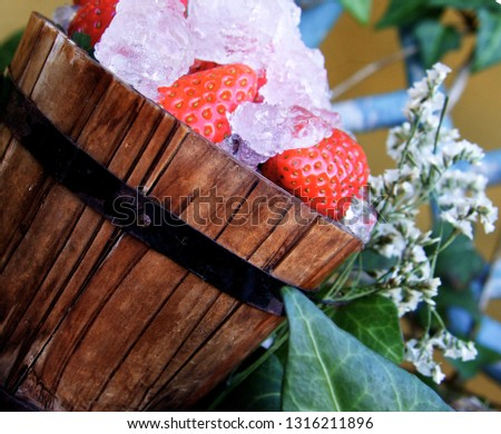Bucket with strawberries and flowers