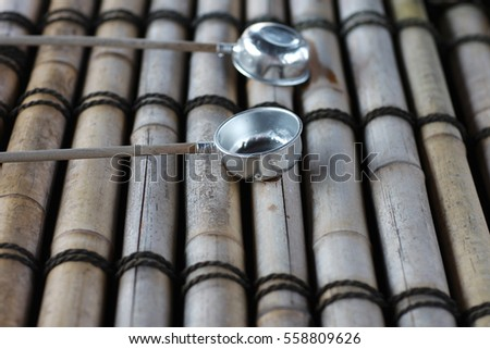 Buckets for washing hands before visiting a temple made of stainless steel to bamboo pipes. #558809626