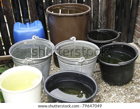 Buckets in zinc and plastic filled with collected rainwater for watering garden