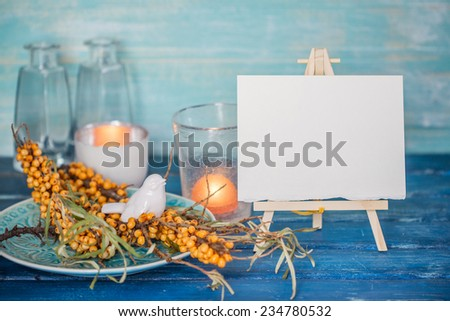 Buckthorn branches with white bird figurine on a blue plate and mini easel with blank canvas