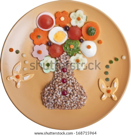 Buckwheat cereal with vegetables, cheese and eggs are laid in the form of a vase with flowers