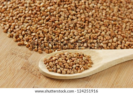 buckwheat groats and wooden spoon on the kitchen table