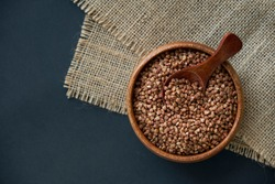 Buckwheat groats in a wooden bowl and vintage scoop. Close up on a black background. copy space for text