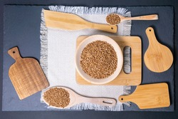 Buckwheat groats in a wooden bowl. Close up on a black background. flat lay