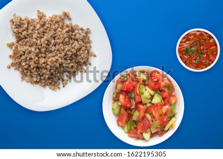 buckwheat in a white plate on a blue background with vegetable salad. buckwheat top view. Healthy food. vegetarian food