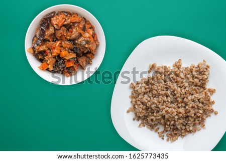 buckwheat in a white plate on a green background with vegetable salad. buckwheat top view. Healthy food. vegetarian food