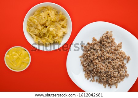 buckwheat in a white plate on a red background with vegetable salad. buckwheat top view. Healthy food. vegetarian food