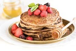 Buckwheat pancakes with berry fruit,honey and sugar powder,selective focus
