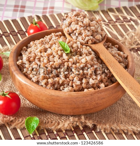 Buckwheat porridge in a wooden bowl - stock photo