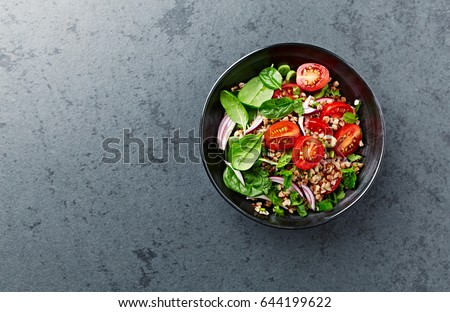 Buckwheat salad with juicy cherry tomatoes, baby spinach, chive, red onion and fresh mint served on stone background. Home made food. Concept for healthy diet and nutrition.Top view.  Copy space.