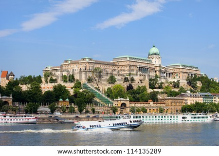 Buda Castle historic landmark and passenger boats on the Danube River in Budapest, Hungary.