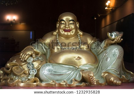 Budai / Hotei, smiling fat and obese buddhist monk - symbol of hapinness, consumeric pleasure. Shiny and Glossy statue and sculpture of belly asian male. (low depth of field)