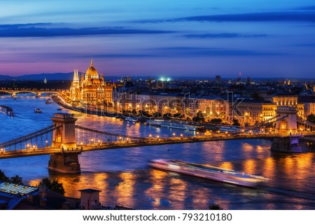 Budapest city at blue hour twilight with illuminated Chain Bridge and Hungarian Parliament on Danube River, tranquil evening cityscape.