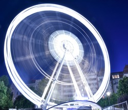Budapest Eye - long exposure photo of a spinning and illuminated ferris wheel at night, motion blur and light trails- amusement park evening, cityscape