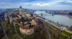 Budapest, Hungary - Aerial drone skyline view of Buda Castle Royal Palace with Szechenyi Chain Bridge and Parliament of Hungary on a cloudy winter day
