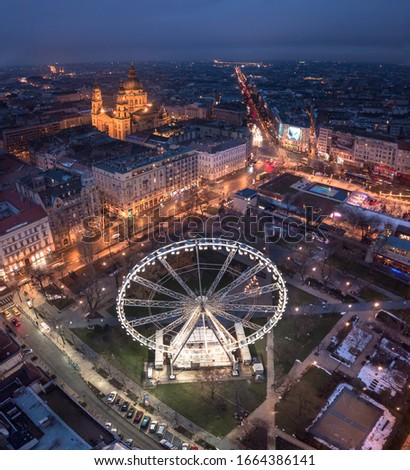 Budapest, Hungary - Aerial drone view of Elisabeth square at blue hour with illuminated ferris wheel and St. Stephen's Basilica at background. Summer evening in Budapest Stock fotó ©