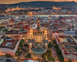Budapest, Hungary - Aerial drone view of the famous illuminated St.Stephen's Basilica (Szent Istvan Bazilika) at blue hour. Buda Castle, Szechenyi Chain Bridge and Fisherman's Bastion at background