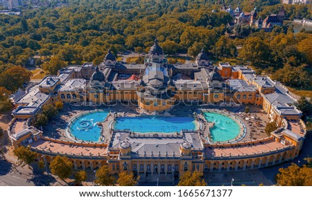 Budapest, Hungary - Aerial drone view of the famous Szechenyi Thermal Bath and Spa on a sunny summer day. Heroes' Square, Vajdahunyad Castle and Buda Hills at background. Stock fotó ©