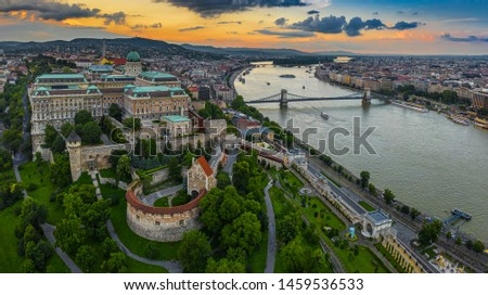 Budapest, Hungary - Aerial panoramic skyline view of Buda Castle Royal Palace with Matthias Church, Szechenyi Chain Bridge and Parliament building with a beautiful orange sunset at summer time #1459536533