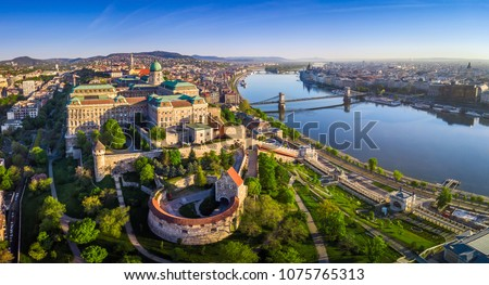 Budapest, Hungary - Aerial panoramic skyline view of Buda Castle Royal Palace with Szechenyi Chain Bridge, St.Stephen's Basilica, Hungarian Parliament and Matthias Church at sunrise with blue sky #1075765313