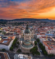 Budapest, Hungary - Aerial panoramic skyline view of St. Stephen's Basilica with a dramatic colorful sunset and Szechenyi Chain Bridge, Buda Castle Royal Palace, Buda Hills at background