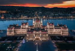Budapest, Hungary - Aerial panoramic view of the beautiful illuminated Hungarian Parliament building at blue hour with Christmas tree. Buda Hills and River Danube at background on a December evening
