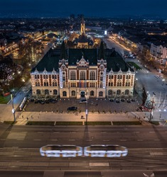 Budapest, Hungary - Aerial panoramic view of Ujpest city centre with City Hall building, St. Stephen's square and church, Christmas tree and light tram on the move taken on a December evening