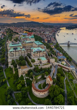 Budapest, Hungary - Aerial skyline view of Buda Castle Royal Palace with Matthias Church, Szechenyi Chain Bridge and Buda Hills with a beautiful orange sunset at summer time #1440784721