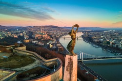 Budapest, Hungary - Aerial skyline view of Statue of Liberty with Buda Castle Royal Palace and Chain Bridge at background. Morning sunrise with blue sky and clouds