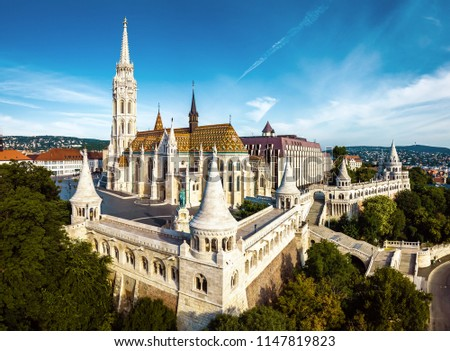 Budapest, Hungary - Aerial view of famous Fisherman's Bastion (Halaszbastya) and Matthias Church (Matyas templom) in the summer morning with Buda Hills at background. Vintage version #1147819823