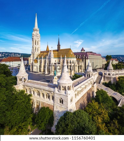 Budapest, Hungary - Aerial view of famous Fisherman's Bastion (Halaszbastya) and Matthias Church (Matyas templom) in the morning with Buda Hills at background #1156760401