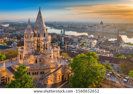 Budapest, Hungary - Beautiful golden summer sunrise with the tower of Fisherman's Bastion and green trees. Parliament of Hungary and River Danube at background. Blue sky. Сток-фото ©