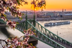 Budapest, Hungary - Beautiful spring sunrise at Liberty Bridge with cruise ship on River Danube and Cherry Blossom at foreground