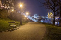 Budapest, Hungary - Bench and lamp post in a park at Buda district with Szechenyi Chain Bridge and Parliament at background at winter time