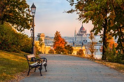 Budapest, Hungary - Bench at Varkert Bazaar with lamp post, autumn foliage, Szechenyi Chain Bridge and Parliament at background on a warm autumn morning